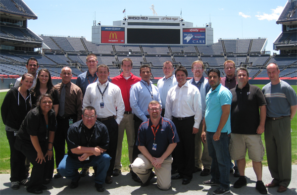 INVESCO Field at Mile High IDP attendees pose for a photo under the famous Bronco atop the stadium video board.