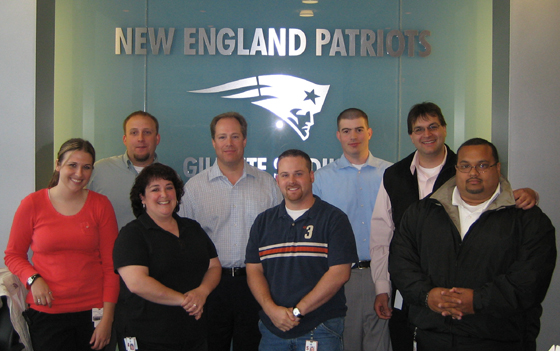 TEAM IDP participants proudly stand in front of the New England Patriots logo welcoming all guests to Gillette Stadium