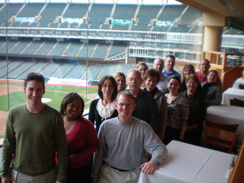 TEAM IDP participants pose in the club level overlooking a snowy Progressive Field