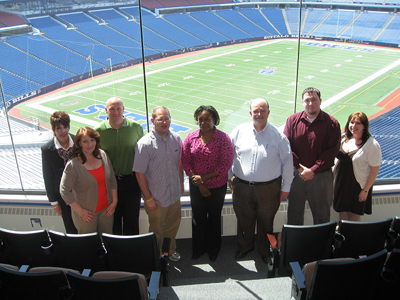 Ralph Wilson Stadium IDP attendees in front of an iconic photo.